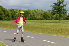 Little girl rolller skating in a park Stock Image