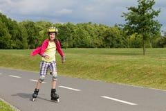Little girl rolller skating in a park Stock Image