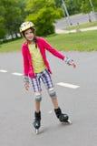 Little girl rolller skating in a park Royalty Free Stock Image