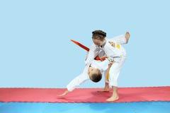 Little girl rolls boy on the mats Stock Images