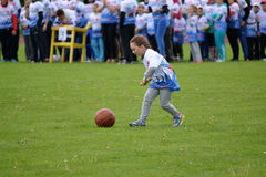 The little girl rolls before  herself a ball by means of a stick at the competitions Cheerful Starts Royalty Free Stock Images