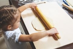 Little girl rolls out the dough with a big rolling pin Stock Image