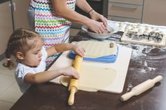 Little girl rolls out the dough, while her mother stirs the ground meat for cooking dumplings.  stock photo