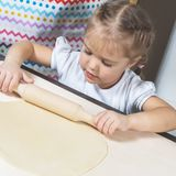 A little girl rolls out the dough using a wooden rolling pin at home Royalty Free Stock Photography