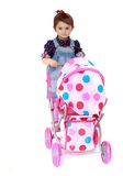 Little girl rolls the stroller Stock Photo