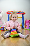 Little girl in a room with toys Stock Photos