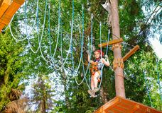 Little girl on a ropes course in a treetop adventure park passing hanging rope obstacle stock images