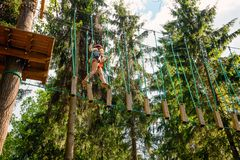 Little girl on a ropes course in a treetop adventure park passing hanging rope obstacle royalty free stock photos