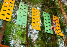 Little girl on a ropes course in a treetop adventure park passing hanging rope obstacle stock photos