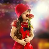 Little girl with rose. People, happiness concept. Happy little girl with rose in red clothes Stock Photo