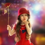 Little girl with rose sends kiss. People, happiness concept. Happy little girl with rose in red clothes sends kiss her hand Stock Photo