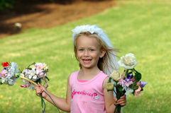 Little girl with roses. A beautiful little Caucasian blond happy girl child with blue eyes laughing and holding flowers in her white hands running in the park royalty free stock images
