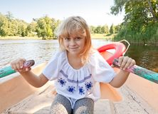 Little girl rowing on the boat Royalty Free Stock Photos