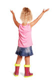 Little girl in rubber boots with her hands raised standing. Royalty Free Stock Photography