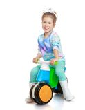 Little girl in rubber boots is riding on a little Royalty Free Stock Photo