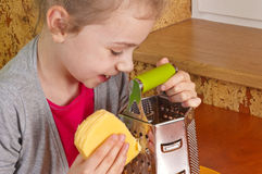 Little girl rubs cheese Royalty Free Stock Image