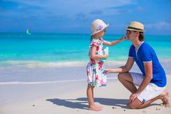 Little girl rubs sunscreen on nose of her dad Stock Photos