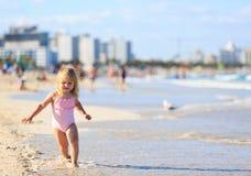 Little girl run play with waves on the beach Stock Photos