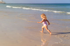Little girl run play with waves on the beach Royalty Free Stock Photos
