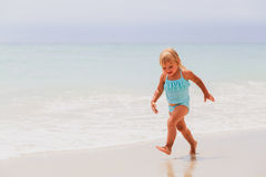 Little girl run play with waves on the beach Royalty Free Stock Image