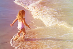 Little girl run play with waves on the beach Royalty Free Stock Photo