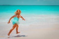 Little girl run play with waves on the beach stock photo