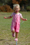 Little girl running. A blue eyed and blond active little toddler girl in pink clothes with happy expression in the beautiful face running towards other kids and Royalty Free Stock Photo