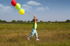 Little girl running. With balloons Stock Photography