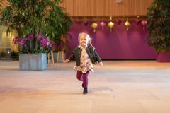 Little girl running indoors with magenta wall in background. Little girl running across room at an indoor garden show Royalty Free Stock Photography
