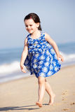 Little Girl Running Along Beach Stock Photo