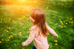 Little girl running along the green lawn with yellow dandelions, back view. Royalty Free Stock Photography