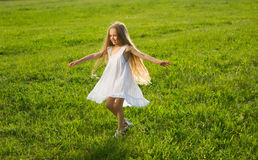 Little girl running along the meadow. Stock Image