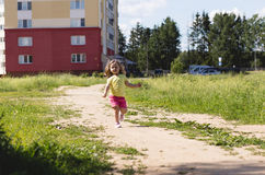 The little girl is running along the road Royalty Free Stock Photo