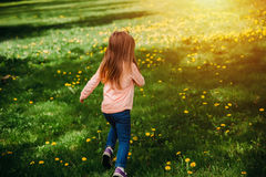 Little Girl Running Along The Green Lawn With Yellow Dandelions, Back View. Stock Photo