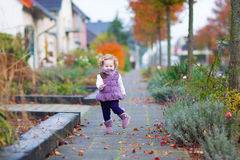Little girl running in an autumn street Stock Image