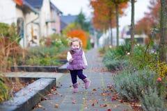 Little girl running in an autumn street Stock Image