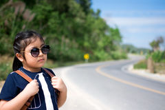 Little girl running away on the road ahead Royalty Free Stock Images