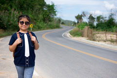 Little girl running away on the road ahead.  Royalty Free Stock Photography