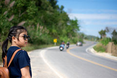Little girl running away on the road ahead.  stock image