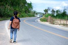 Little girl running away on the road ahead.  royalty free stock photo