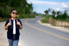 Little girl running away on the road ahead Royalty Free Stock Photo