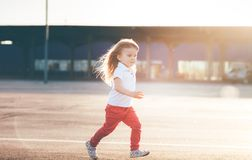Little girl running away on the road stock images