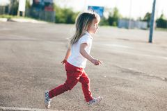 Little girl running away on the road Royalty Free Stock Image