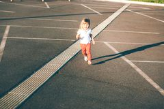 Little girl running away on the road Stock Photography