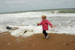 Little girl running away from the sea Stock Photos