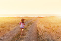 Little girl running in backlit meadow Stock Photography