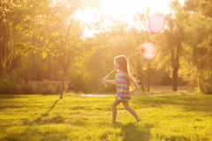 Little girl running with a balloon. Little girl with a balloon runs on lawn in the park outdoors. Freedom and carefree Royalty Free Stock Image