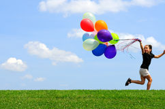 Little Girl Running with Balloons. Little girl running with with colorful helium balloons. Green grass, blue sky background Royalty Free Stock Images