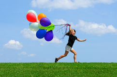 Little Girl Running with Balloons. On top of the hill. Green grass, blue sky background Stock Image