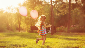 Little girl running with balloons. Little girl with balloons running on the lawn in the park outdoors. Freedom and carefree. Happy childhood Royalty Free Stock Images